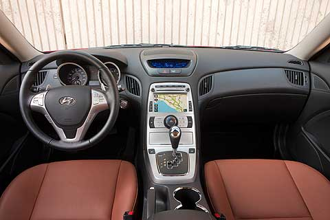 The Hyundai Genesis Coupe boasts a cockpit designed to enhance the driving experience. Analog gauges include a large speedometer and tachometer positioned so the driver can immediately access critical driving information